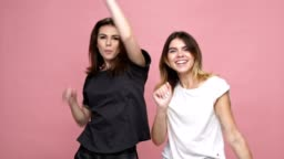 Two young cheerful girls jumping from a side and starting to dance isolated over pink background