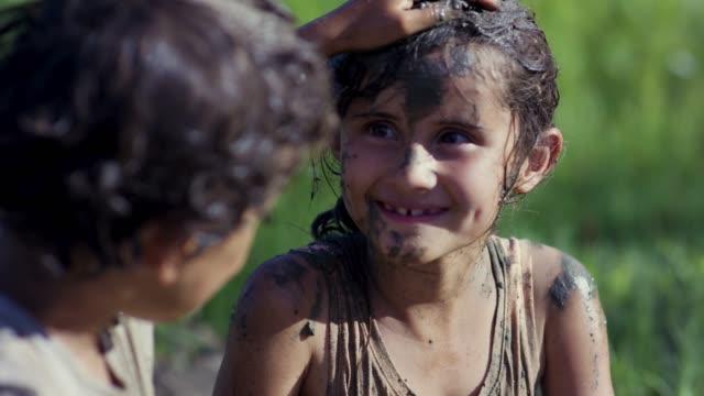 楽しみに参加している 2 人の若い子供の泥の実行 - 障害物コース点の映像素材/bロール