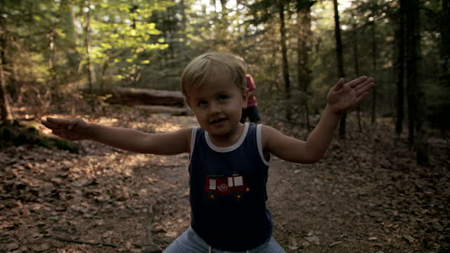stockvideo's en b-roll-footage met twee jonge kinderen die in het bos samen spelen - hoofddeksel