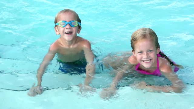 vídeos de stock, filmes e b-roll de duas crianças nadando na piscina - irmão