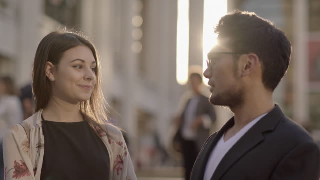 vidéos et rushes de two young colleagues meeting in the city talking together. urban people lifestyle background - châle