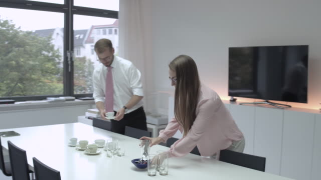 Two young colleagues setting the table for a business meeting