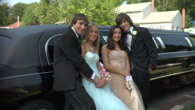 MS, Two young couples in prom attire posing beside limo, portrait, Edison, New Jersey, USA