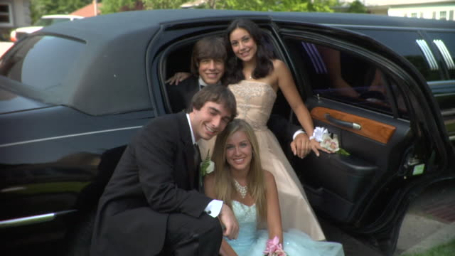 MS, Two young couples in prom attire posing in limo, portrait, Edison, New Jersey, USA