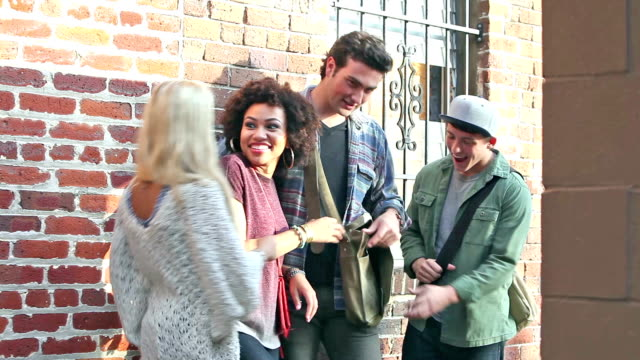 two young couples laughing, looking in bag - shoulder bag stock videos & royalty-free footage