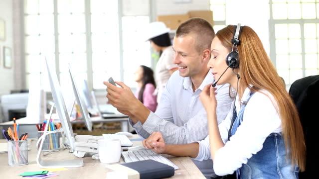 Zwei HD junge Mitarbeiter, die Spaß im modernen Büro