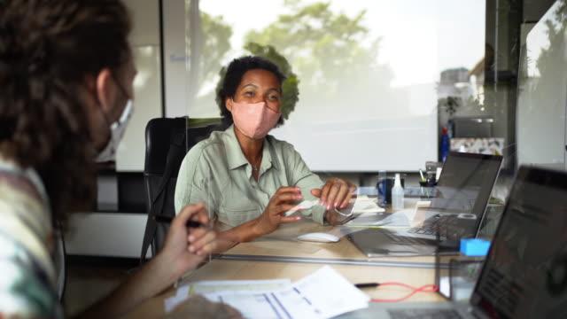 vidéos et rushes de deux jeunes collègues planant leur travail au bureau pendant la pandémie - ressources humaines