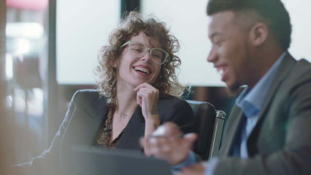 two young creative business coworkers laugh and smile during a team meeting - colleague stock videos & royalty-free footage