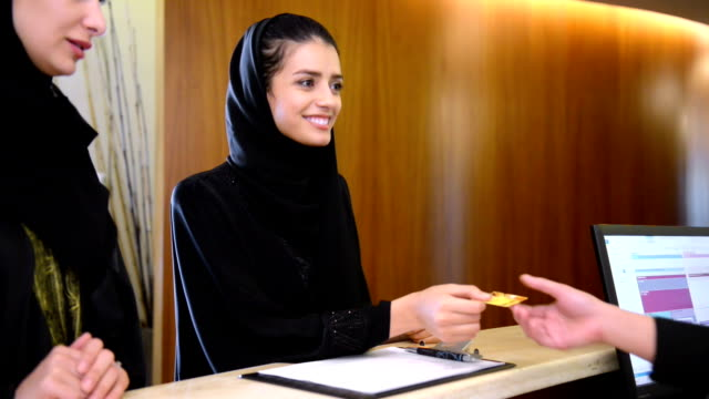 Two young Emirati women paying via credit card