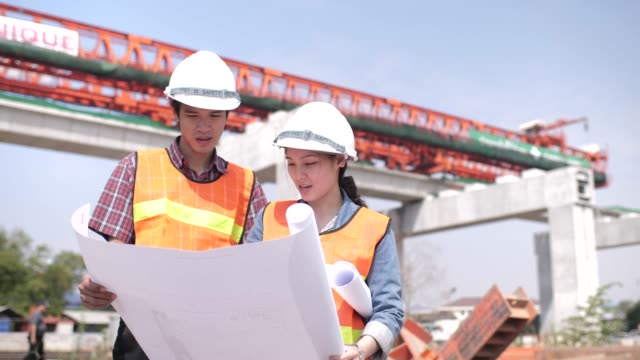Two young engineers talking with together in construction site , background big crane , they wearing safety equipment