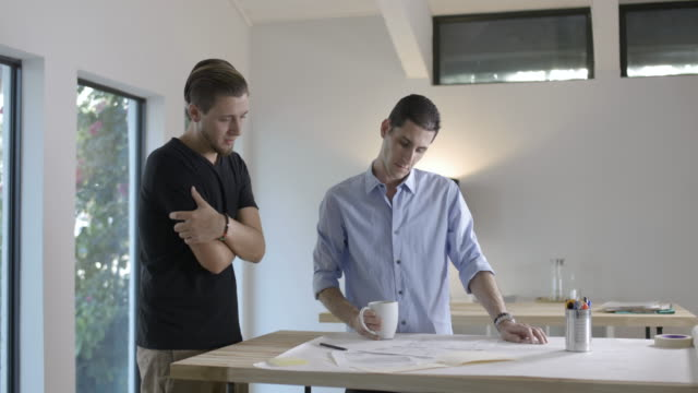 Two young entrepreneurs standing at desk looking at project notes together.