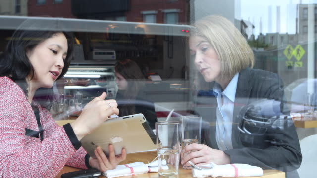 Two young, female business executives having a business lunch.