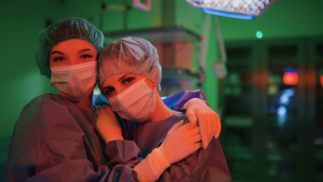two young female doctors hug and look at you - nurse cap stock videos & royalty-free footage