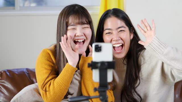 2人の若い女性の友人が自宅でスマートフォンでソーシャルメディアでライブストリーミング - millennial generation点の映像素材/bロール
