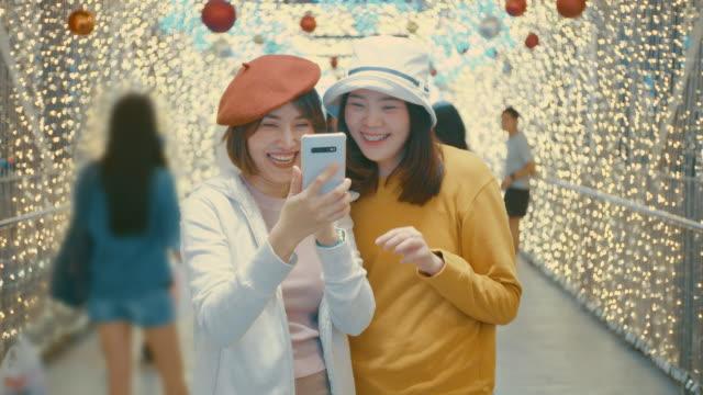 zwei junge weibliche touristen genießen ein selfie mit einem handy zu weihnachten,slow-motion - besonderes lebensereignis stock-videos und b-roll-filmmaterial
