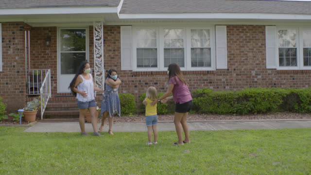 two young friends embrace each other while maintaining social distance - neighbor stock videos & royalty-free footage