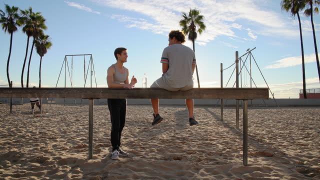 vidéos et rushes de deux jeunes amis, latino et caucasien-blanc, s'asseyant et se reposant à l'espace sportif extérieur de plage de muscle après l'exercice de forme physique. venice beach, santa monica, los angeles, californie, etats-unis. - trentenaire