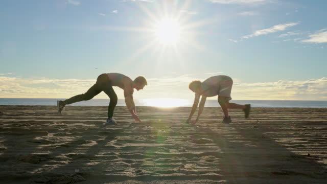 vidéos et rushes de deux jeunes amis, latinx et hommes caucasiens-blancs, faisant l'entraînement de push-up de forme physique sur la plage de venise au coucher du soleil. santa monica, californie, etats-unis. - 30 34 ans