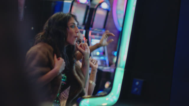 two young friends playing slot machines at a casino in las vegas win and jump up and down and hug in celebration - warm clothing stock videos & royalty-free footage