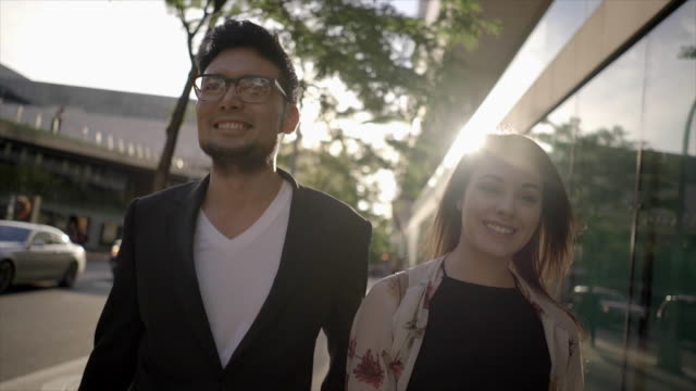 two young friends walking in the city having fun together. urban lifestyle scene of asian man and caucasian women