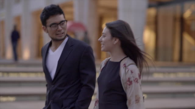 vidéos et rushes de two young friends walking in the city having fun together. urban lifestyle scene of asian man and caucasian women - plan en travelling