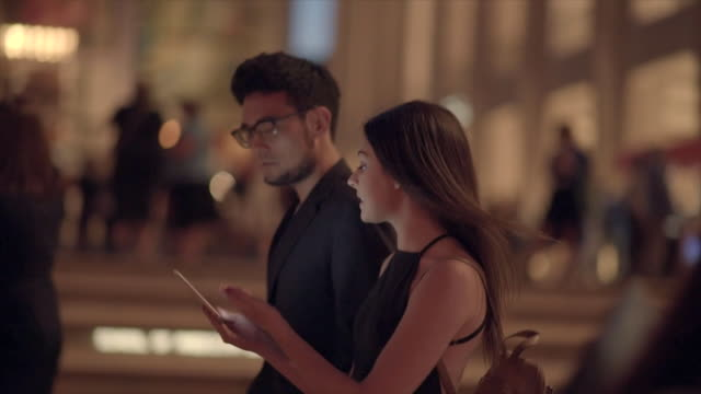 vidéos et rushes de two young friends walking in the city looking at tablet computer screen. urban lifestyle scene of asian man and caucasian women - regarder vers le bas