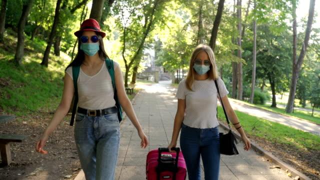 vídeos y material grabado en eventos de stock de dos jóvenes amigos con máscara protectora caminando por el parque - neumonía