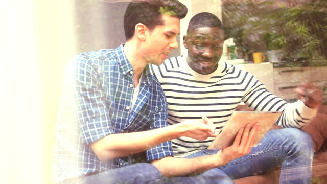 MS Two young gay men using digital tablet