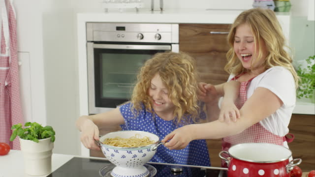 two young girls cooking together