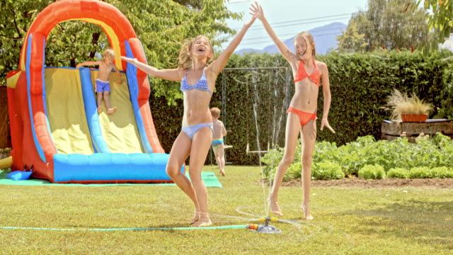 slo mo two young girls dancing around water sprinkler - water slide stock videos & royalty-free footage