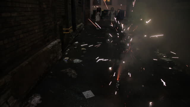 ms tu two young girls having fun and lighting fireworks and sparklers at night in alley together / minneapolis, minnesota, united states - cracker stock videos and b-roll footage