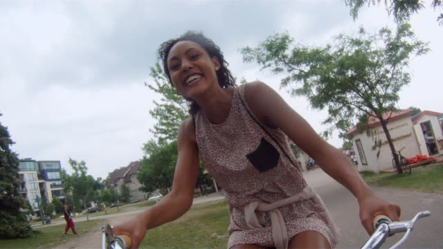 MS POV Two young girls having fun and riding bicycles in urban area near lake and inside park / Minneapolis, Minnesota, United States