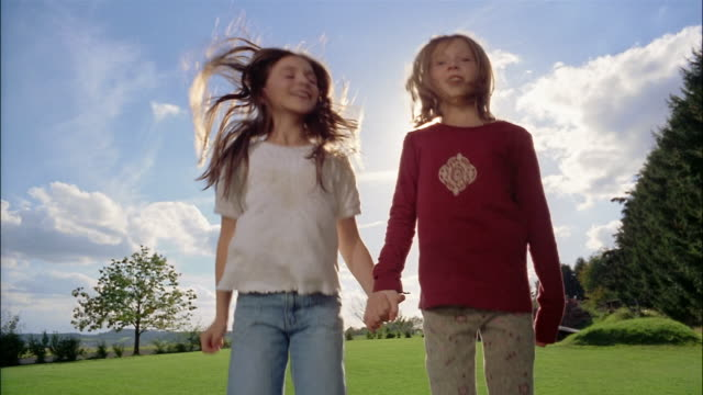 Two young girls hold hands and jump on a trampoline.