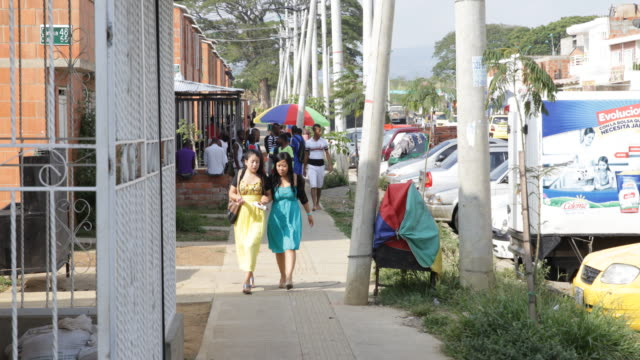 Two young girls in colorful dresses walking down a street a fence for protection for a shop can be seen on the left side