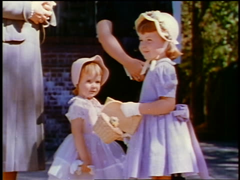 1957 two young girls in dresses + bonnets standing by two women outdoors / feature - 1957 stock videos & royalty-free footage