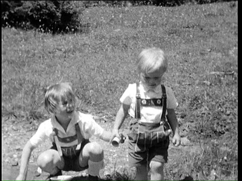 1937 b/w montage two young girls in traditional bavarian lederhosen playing on alpine meadow / bavaria, germany - german culture stock videos & royalty-free footage