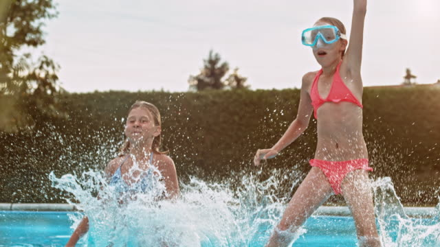 slo mo two young girls jumping into pool holding hands - swimwear stock videos & royalty-free footage