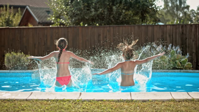 slo mo ds two young girls jumping into the pool - fence stock videos & royalty-free footage