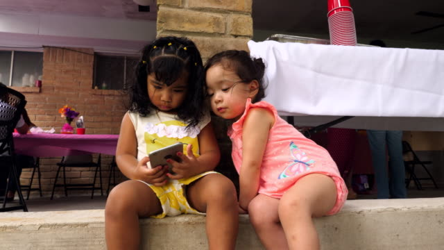 MS Two young girls looking at smartphone during birthday party