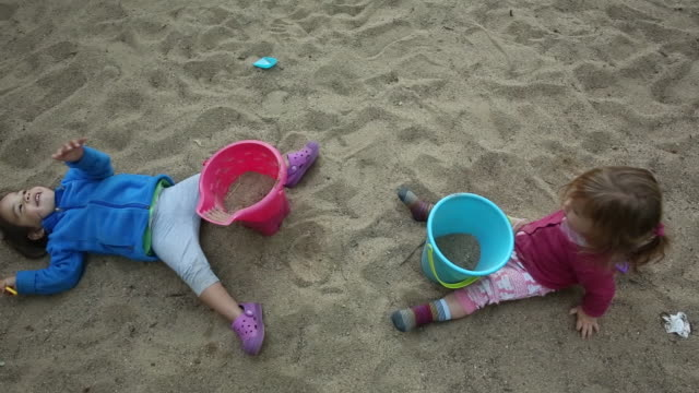 vidéos et rushes de two young girls playing in the sand with buckets and shovels. - 2 kid in a sandbox