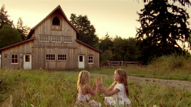 two young girls playing pattycake in field in front of barn - barn stock videos & royalty-free footage
