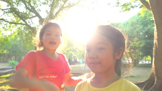 vidéos et rushes de deux jeunes filles jouant avec regardant l'appareil-photo dans le parc - série d'émotions
