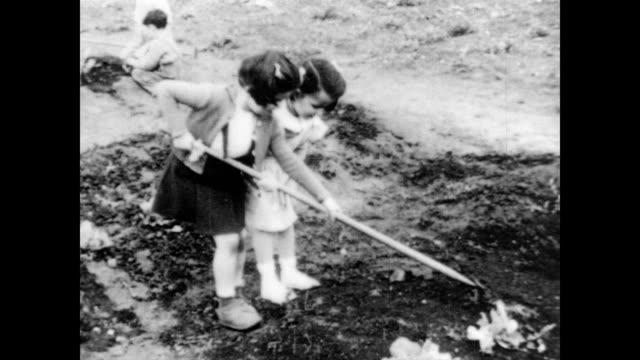 / two young girls pull a hoe across the dirt in a vegetable garden children in the garden on january 01 1940 in unspecified - garden hoe stock videos & royalty-free footage