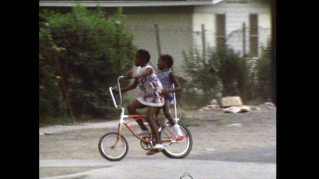 two young girls ride a bike in los angeles; 1972 - bbc archive stock-videos und b-roll-filmmaterial