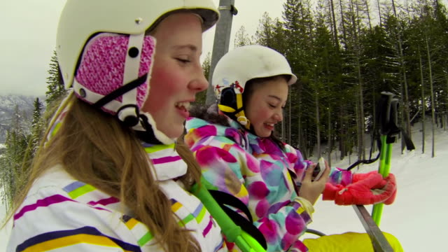 2 つの若い女の子乗りチェアリフトのスキー場 - glove点の映像素材/bロール