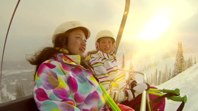 two young girls riding chair lift at ski hill - ski lift stock videos & royalty-free footage
