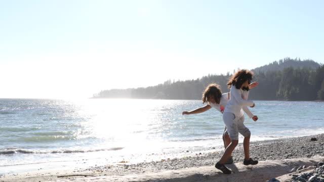 vídeos de stock, filmes e b-roll de duas meninas corram log de praia, trocar de lugar - cabelo encaracolado