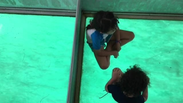 two young girls sit and sail on a glass bottom boat - cook islands stock videos & royalty-free footage