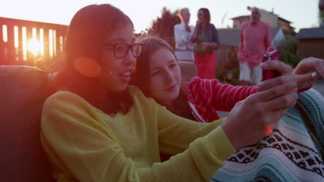 MS Two young girls sitting on couch on patio in backyard of home looking at smartphone during party on summer evening