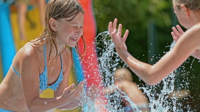 rallent tu due giovane ragazza spruzzi d'acqua in casa - 8 9 anni video stock e b–roll